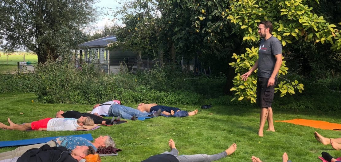 Marius Helf teaching a breathing session on a green lawn