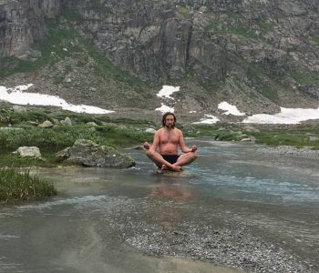 Marius Helf practicing the Wim Hof Method in an icy river surrounded by snow covered mountains